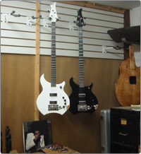 The Black & White Sibling Basses Hanging In Shop